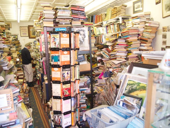 This wonderfully cluttered bookshop in Tenby, Wales, UK is precisely the sort of mess that Google Books tries to solve. In the bookstore, there is no search, no apparent organization whatsoever (except those lovely Penguin classics in the spinner rack). On Google Books, every word of every book is part of a searchable database. (Photo by Howard Blumenthal, all rights reserved, do not duplicate or distribute without written permission.)