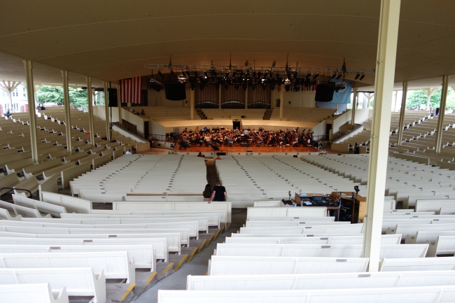 The amphitheater, orchestra on stage, rehearsing. Note the houses nearby (left and right). The amphitheater is just another site in the Chautauqua neighborhood.